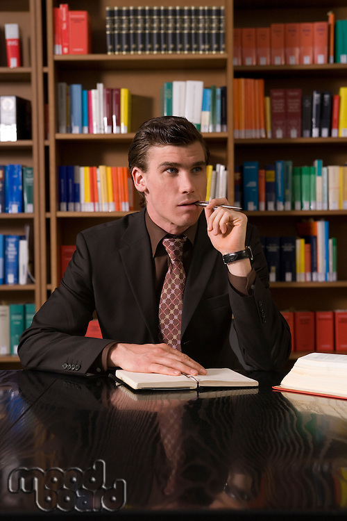 Man wearing suit chewing pen at desk in library