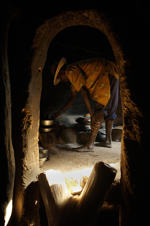 Boukoumbe December 2006 - A man cooks inside of his home in Boukoumbe, Benin.  The home is built in the Tata Somba architectural style. © Jean-Michel Clajot