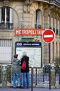Tourists on foot study Metropolitain subway map for the Paris Metro in Rue du Bac, Left Bank, Paris, France