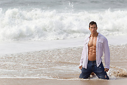 sexy man in an open shirt and jeans in the ocean