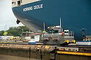 Locomotive and detail of stern of cargo ship at Miraflores locks. Panama Canal, Panama City, Panama, Central America.