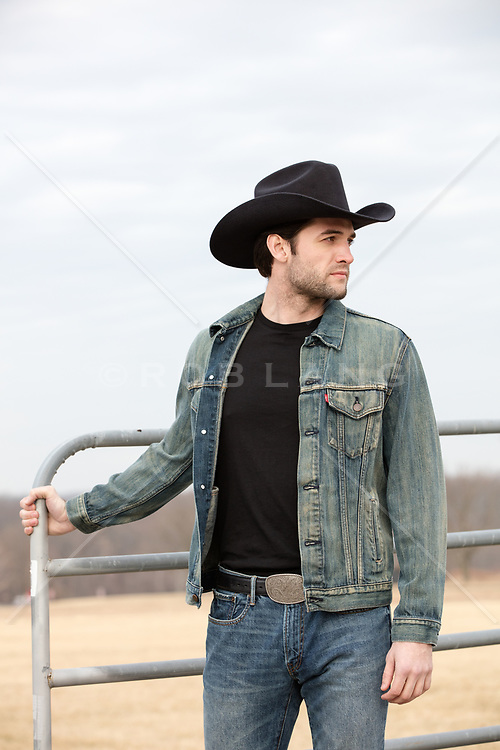 cowboy holding a gate on a ranch