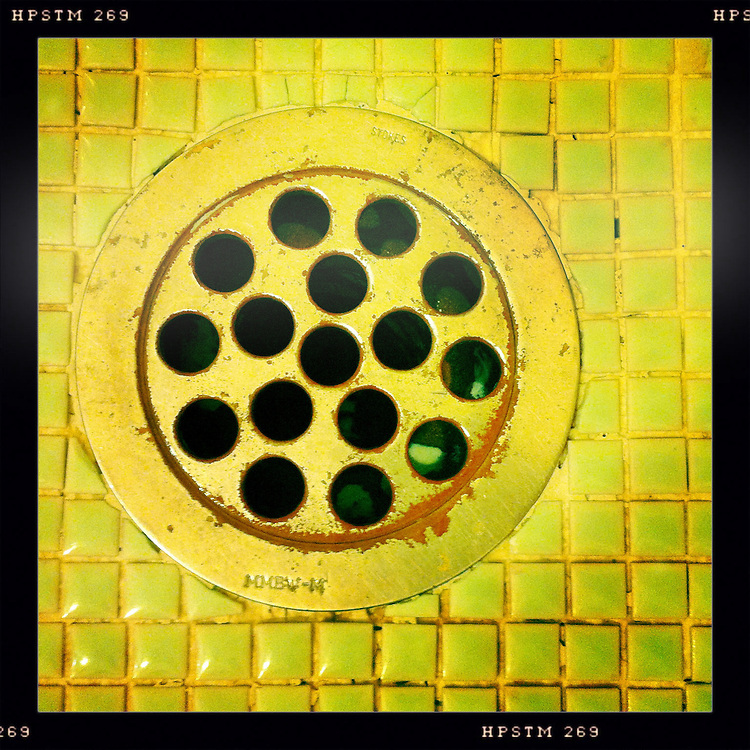 A grubby-looking drain hole with small square mosaic tiles