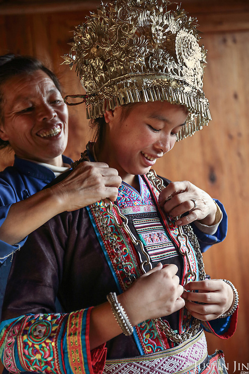 For the first time in her life, Mrs Wu dresses her daughter in the costume she weaved for her, to celebrate her daughter's university entrance. ..According to Dong traditions, a mother makes the dress while she is still pregnant in anticipation of a major happy event in the girl's adult life.