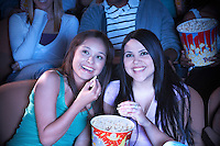Two young women sharing popcorn in cinema