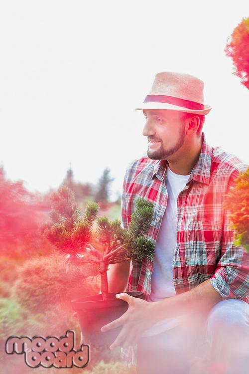 Portrait of handsome gardener wearing hat while holding flower pot in the garden