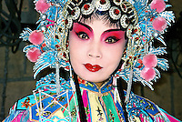 China, Taiyuan, 2003. A female Chinese opera performer waits in the wings for her entrance. Traditional costumes can often be quite heavy, and makeup elaborate.