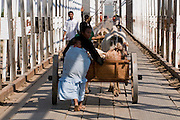 Woman pushing a horse cart above the Steelbridge above the Mandrare river, Madagascar, Africa
