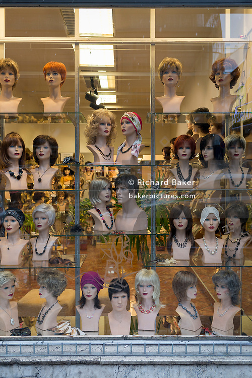 Assorted wigs on mannequin heads in a shop window on Vodickova Street, on 17th March, 2018, in Prague, the Czech Republic.