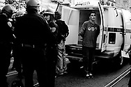 handcuffed demonstrators await to be transported to the station, San Francisco, 2004
