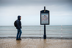 © Licensed to London News Pictures. 2/05/2016. CAberystwyth, Wales, UK.  A man out walking in the rain on the deserted promenade on a dismal,  mild ,wet and grey  Bank Holiday Monday in Aberystwyth Wales. Photo credit: Keith Morris/LNP