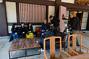 """Priest Matsumoto Shoukei drinking tea and talking with participants while being filmed at a """"Temple Morning"""" cleaning session. Komyoji Temple, Kamiyacho, Tokyo, Japan, April 13, 2019. Matsumoto Shoukei is the author of A Monk's Guide to a Clean House and Mind (Penguin). He hold periodic cleaning sessions at his temple in Tokyo's Kamiyacho district."""