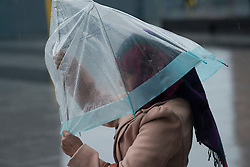 Christmas Storm Weather. A woman struggles with an umbrella in heavy rain and strong wind at King's Cross Station, London. Kings Cross, London, United Kingdom. Monday, 23rd December 2013. Picture by Peter Kollanyi / i-Images