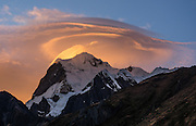 Golden sunrise light hits lenticular (lens-shaped, UFO-like) clouds capping Nevado Yerupaja Grande (6635 m or 21,770 ft), Peru's second highest peak. Seen from Incahuain / Jahuacocha campground on Day 9 of 9 days trekking around the Cordillera Huayhuash in the Andes Mountains, one day's walk from LLamac village, Peru, South America.