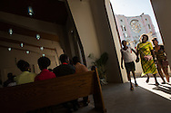 Attendees enter a newly constructed worship hall next to Notre Dame de l'Assomption-- the main cathedral in Port-au-Prince, Haiti-- next to the destroyed building during a Sunday Catholic Mass, January 4, 2015.  The original church will be reconstructed, with a modern design by Puerto Rican firm Segundo Cardona and a team of six other architects, which won the contract which was chosen from among 134 proposals.