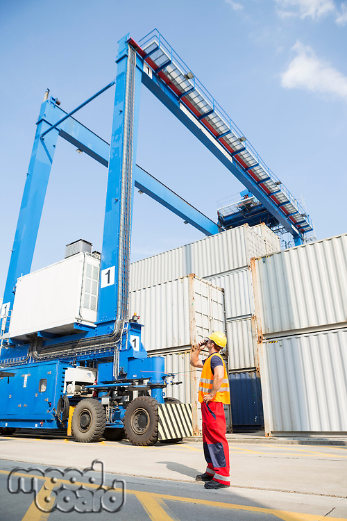 Full-length of worker using walkie-talkie in shipping yard