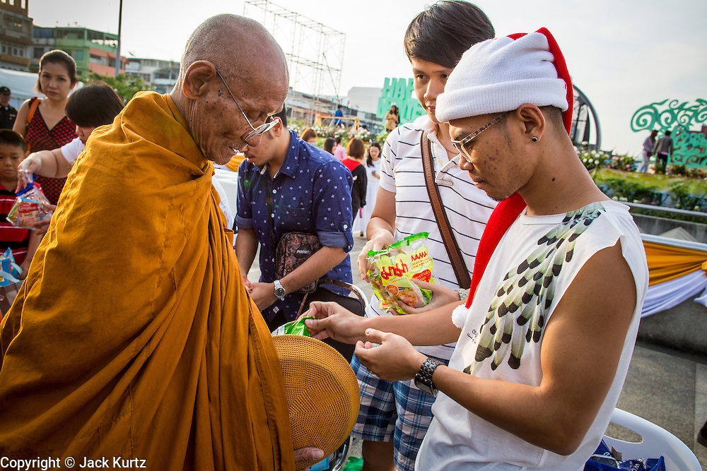 """01 JANUARY 2013 - BANGKOK, THAILAND:  A Thai teenager in a Santa hat presents a Buddhist monk with an offering during a special merit making ceremony at Bangkok City Hall New Year's morning. Many Thais go to Buddhist temples and shrines to """"make merit"""" for the New Year. The traditional Thai New Year is based on the lunar calender and is celebrated in April, but the Gregorian New Year is celebrated throughout the Kingdom.     PHOTO BY JACK KURTZ"""