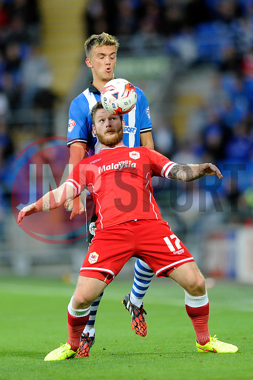 Cardiff City's Aron Gunnarsson holds the ball up against Wigan Athletic's Emyr Huws - Photo mandatory by-line: Dougie Allward/JMP - Mobile: 07966 386802 19/08/2014 - SPORT - FOOTBALL - Cardiff - Cardiff City Stadium - Cardiff City v Wigan Athletic - Sky Bet Championship