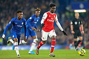 Arsenal midfielder Bukayo Saka (77) pursued by Chelsea midfielder Callum Hudson-Odoi (20) during the Premier League match between Chelsea and Arsenal at Stamford Bridge, London, England on 21 January 2020.