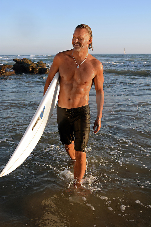 Author and fitness expert, Craig Cooper photographed walking on the beac with his surf board in Newport Beach for his upcoming Book, The New Prime. Newport Beach, California, USA, North America