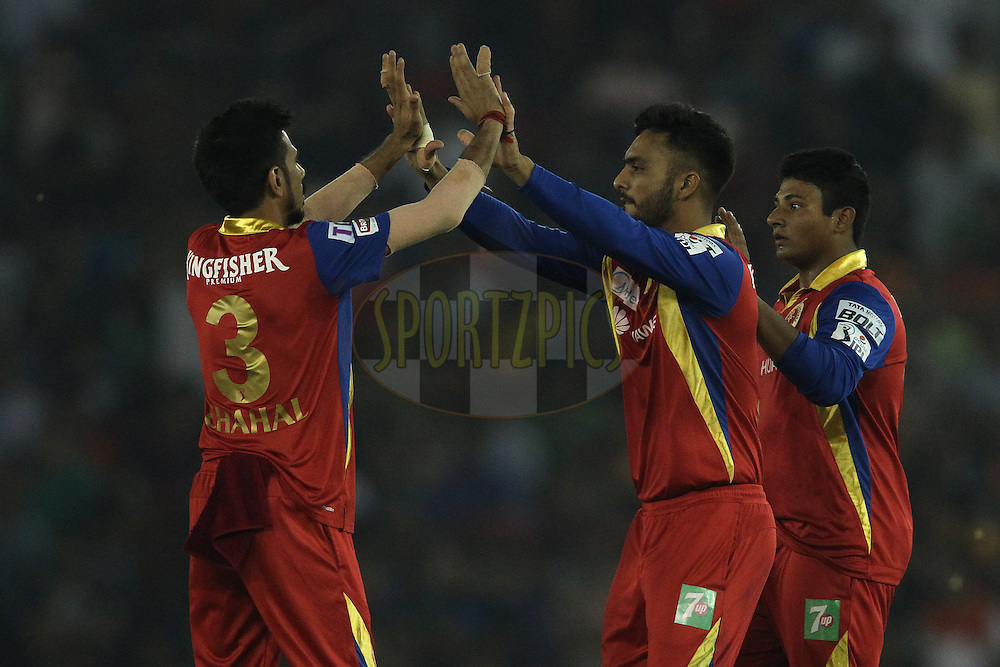 Yuzvendra Chahal of the Royal Challengers Bangalore congratulates Mandeep Singh of the Royal Challengers Bangalore for taking the catch to get Wriddhiman Saha of Kings XI Punjab wicket during match 50 of the Pepsi IPL 2015 (Indian Premier League) between The Kings XI Punjab and The Royal Challengers Bangalore held at the Punjab Cricket Association Stadium in Mohali, India on the 13th May 2015.<br /> <br /> Photo by:  Shaun Roy / SPORTZPICS / IPL