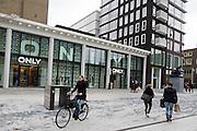 Een fietser rijdt over Plein 1944 langs vestigingen van kledingwinkels Only en MS Mode in het centrum van Nijmegen. Het kledingbedrijf Only is onderdeel van het Deense concern Bestseller. MS Mode is onderdeel van het concern van de Nederlander Ronald Kahn.