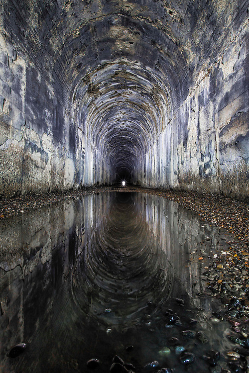 The ceiling of the historic Boulder Tunnel is reflected in a pool of standing water, just last weekend outside of Wickes, Montana.<br />