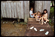 Girls sit on front stoop of shack in Eirunepe slum; note ramp & stilts on house to deal w/ flood Brazil