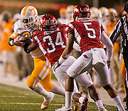 Nov 12, 2011; Fayetteville, AR, USA;  Tennessee Volunteers tailback Tauren Poole (28) is brought down by Arkansas Razorbacks linebacker Jerry Franklin (34) as safety Tramain Thomas (5) looks on during a game at Donald W. Reynolds Razorback Stadium. Arkansas defeated Tennessee 49-7. Mandatory Credit: Beth Hall-US PRESSWIRE