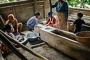Women dehulling rice by hand. This activity is usually done in groups with long wooden sticks that act as pestles. The same sticks are also used to create  percussive music that help the women time their pounding to a rhythm.