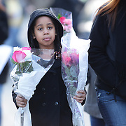 A family with flowers head to the shrine created under the school sign in Sandy Hook after yesterday's shootings at Sandy Hook Elementary School, Newtown, Connecticut, USA. 15th December 2012. Photo Tim Clayton