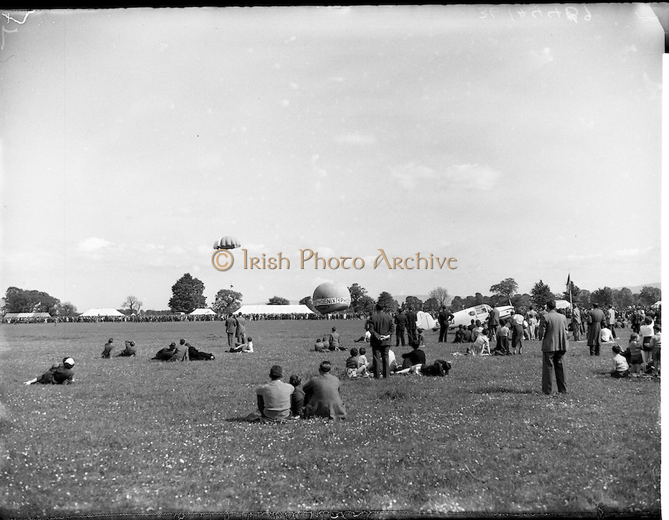 20/05/1956<br /> 05/20/1956<br /> 20 May 1956<br /> Aero Club of Ireland Annual Air Show at Weston airfield, Leixlip, Co. Kildare. spectators watch a parachutist come to land. Note the Phoenix Ale balloon and Miles Messenger aircraft on right.