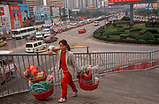 A female worker carries plastic goods on a traditional pole through the centre of Shenzhen, on 10th August 1994, in Shenzhen, China.