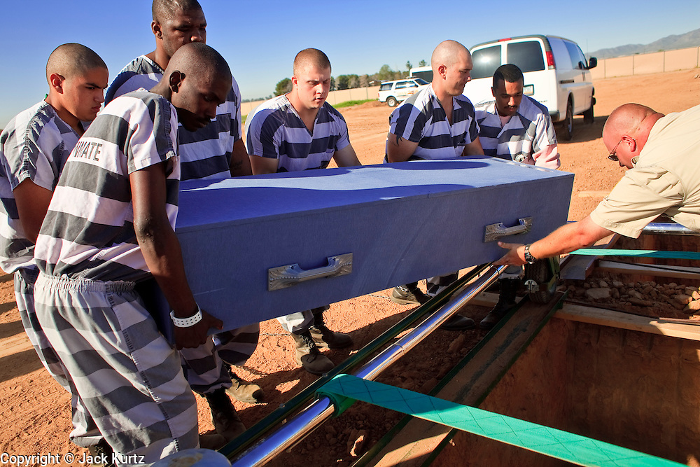 "18 MARCH 2010 - SURPRISE, AZ:  Maricopa County Detention Officer Halucha (CQ) helps inmates bury a person in White Tanks Cemetery on Camelback Rd. in an unincorporated part of the county near Surprise. The county spent about $2.5 million to inter indigent people in what is Maricopa County's ""potters field.""  About 3,000 people, children and adults, are buried in the dusty field west of Phoenix.   PHOTO BY JACK KURTZ"