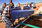"""18 MARCH 2010 - SURPRISE, AZ:  Maricopa County Detention Officer Halucha (CQ) helps inmates bury a person in White Tanks Cemetery on Camelback Rd. in an unincorporated part of the county near Surprise. The county spent about $2.5 million to inter indigent people in what is Maricopa County's """"potters field.""""  About 3,000 people, children and adults, are buried in the dusty field west of Phoenix.   PHOTO BY JACK KURTZ"""