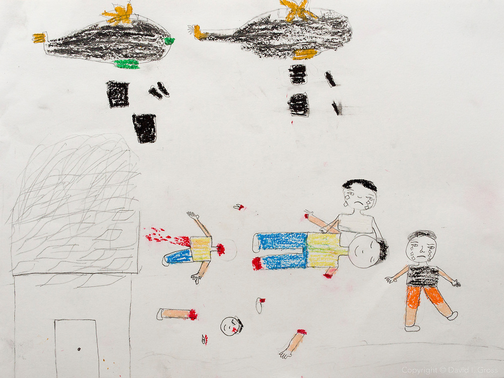 """Two planes drop bombs on the people. The children are crying, and the father has lost his hands."" Drawing by Syrian girl, age 13. (Topic for this session: dealing with loss.) (Note: Arabic writing removed from top-right of image)"