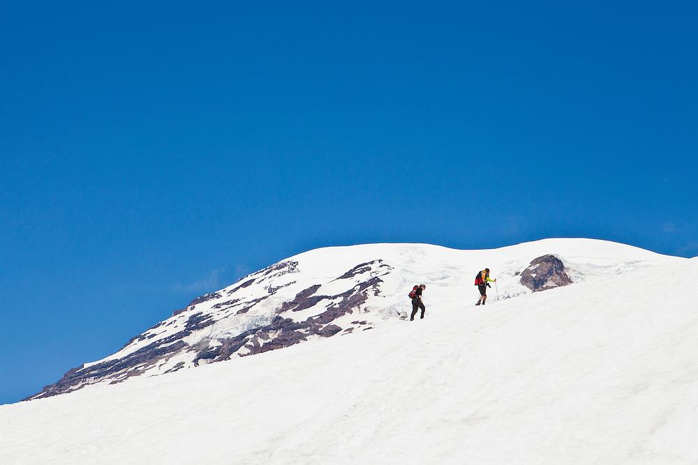 Two climbers make their way up the Muir snow field as they climb Mount Rainier, Washington, USA.