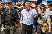 17 FEBRUARY 2014 - BANGKOK, THAILAND: SUTHEP THAUGSUBAN, leader of the Thai anti-government protests, walks past Government House after his followers marched there. The anti-government protest movement, led by the People's Democratic Reform Committee and called Shutdown Bangkok has been going on for more than a month. The protest movement called, the People's Democratic Reform Committee (PDRC), wants to purge the current ruling party and its patrons in the Shinawatra family from Thai politics. The movement has consistently refused any dialogue or negotiations with the Pheu Thai ruling party. Over the weekend Thai police claimed to have taken the protest areas around Government House (the Prime Minister's office) away from protestors but on Monday protestors marched unimpeded to Government House and retook the area.   PHOTO BY JACK KURTZ