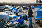 CALAIS, FRANCE - JAN 13: A refugee from Sudan stands on a hill inside the refugee camp known as the 'jungle' in Calais, France on January 13, 2016.