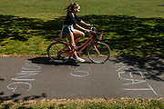 People ride over a positive message - I think you're doing so Great, Considering - written in chalk on the cycle lane - Clapham Common is reasonably busy as the sun is out and it is warmer. The 'lockdown' continues for the Coronavirus (Covid 19) outbreak in London.