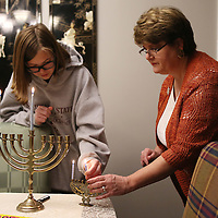 Lauren Wood | Buy at photos.djournal.com<br /> Rebecca Nelson, right, and her daughter Lindsey, 16, put the shamash candle back on the menorah after lighting the first candle on Dec. 6, the first night of Hanukkah at Mimi VanDevender's Tupelo home.