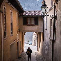 A man holding flowers walks through a narrow cobbled passage in Santa Maria Del Monte in Varese, Italy