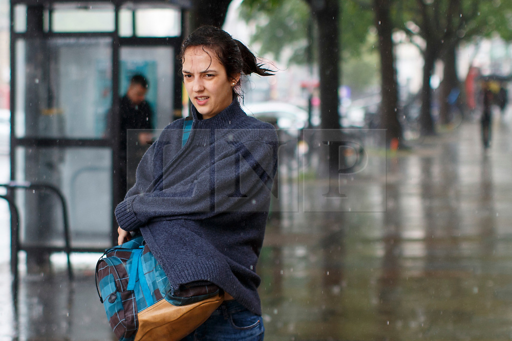 © Licensed to London News Pictures. 23/06/2016. London, UK. A woman drenched in rain tries to take shelter in Islington, London on the polling day of the EU referendum on 23 June 2016. Photo credit: Tolga Akmen/LNP