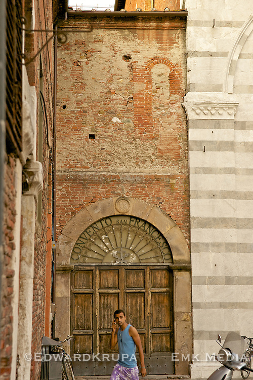 Teenager on a mobile phone with old architecture. Lucca.
