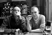 Two teenagers sitting in a coffee shop smoking a spliff and having a beer, Amsterdam, Netherlands, 2000's