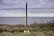© Licensed to London News Pictures. 22/10/2017. Bawdsey, UK.  A yellow container with a radioactive symbol lies against the perimeter fence. RAF Bawdsey, WW2 radar and Cold-War Bloodhound Surface to Air Missile (SAM) base at Bawdsey Ferry, Suffolk, today 22nd October 2017. The base was decommissioned in 1991 leaving behind a deserted base.  Photo credit: Stephen Simpson/LNP