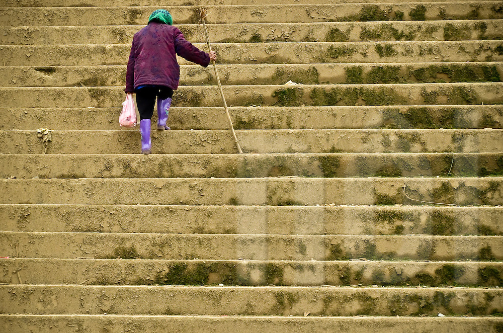 An old woman carrying a plastic bag is climbing stairs using a stick of wood,  at the market of a small village in Lao Cao province, Bac Ha district, North Vietnam.
