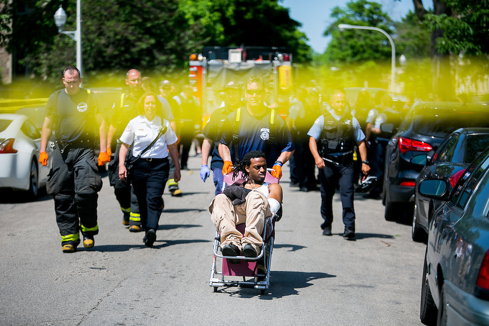 CHICAGO, IL - MAY 30, 2016: A gunshot wound victim is wheeled toward an ambulance at the scene of a shooting near 322 South Hamlin Boulevard in Chicago, Illinois. CREDIT: Sam Hodgson for The New York Times.