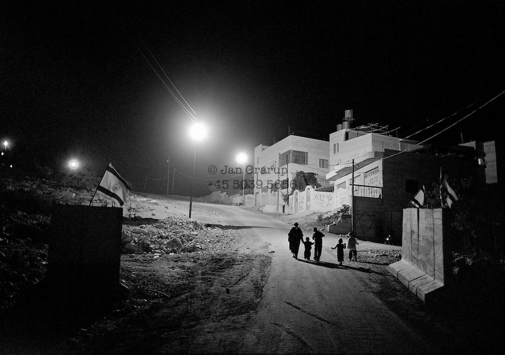 A family returns home to Kiriyat Arba after praying in the synagogue. <br /> Hebron 2001.