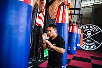 Dejdamrong Sor Amnuaysirichoke, the current ONE Championship strawweight champ, loosens up with a punching bag at Bangkok Fight Lab in Bangkok, Thailand.